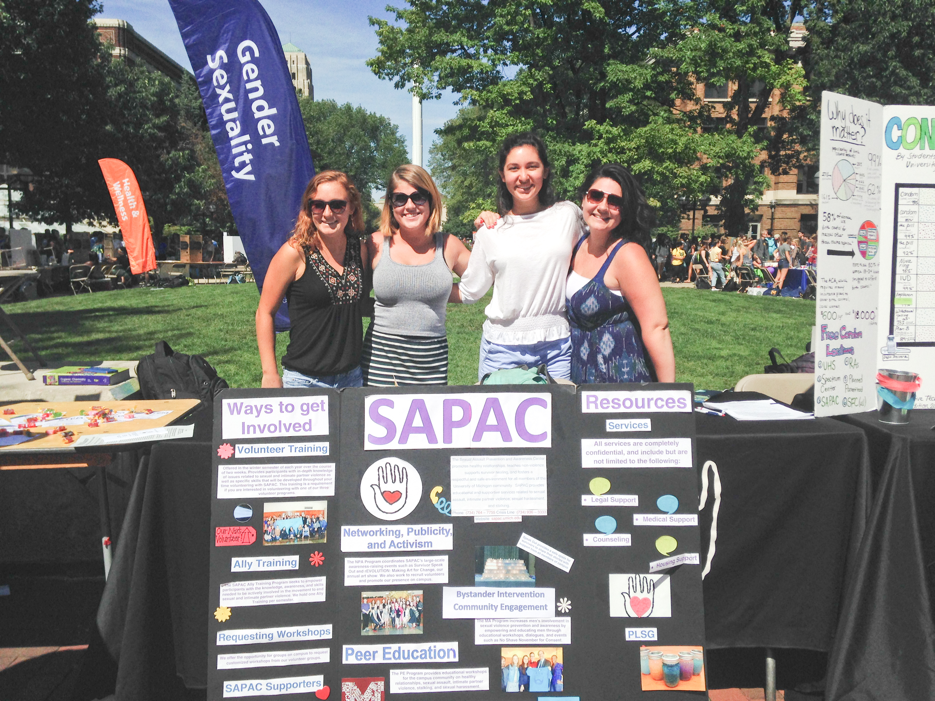 Students stand in the Diag in front of a SAPAC poster