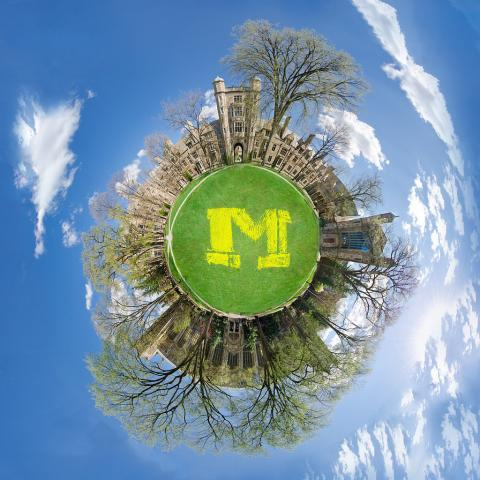 A photograph of the University of Michigan Law Quadrangle that has been digitally edited to look like a small planet