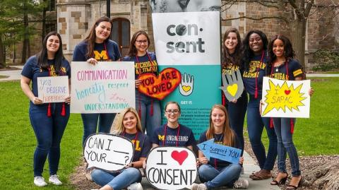 Group of students holding signs that say I heart consent, you are loved, and more posstive messages.