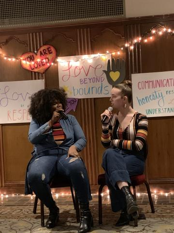 Speakers Corey and Jari sit in front of white fairy lights and signs that say Love Beyond Bounds, You are Loved, and Love is Respect.