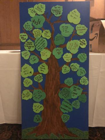 "Painting of a tree with foam leaves stuck to it. The foam leaves have messages of support for survivors written on them. Messages include ""You are loved"" and ""I believe you."""