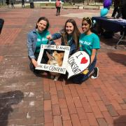 Volunteers pose with Reggie the Campus Corgi and SAPAC signs
