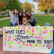 Volunteers posing with corgi and What Does Love Mean to You board