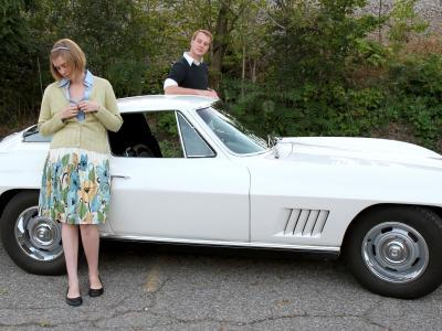Man and a woman standing by a Corvette